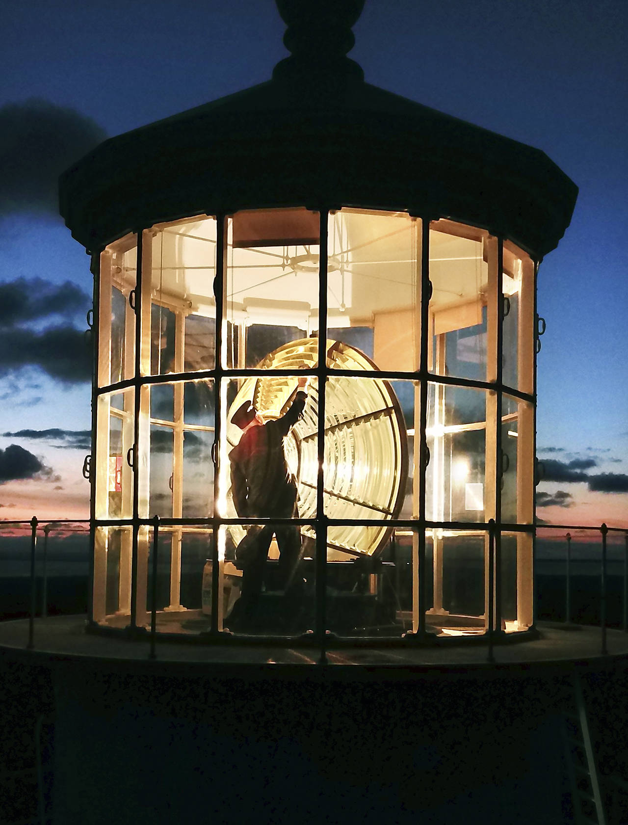 Photo by Pete Lerro                                 Jeff Pence, a member of the Westport-South Beach Historical Society, cleans the Fresnel lens wearing traditional keeper's garb.