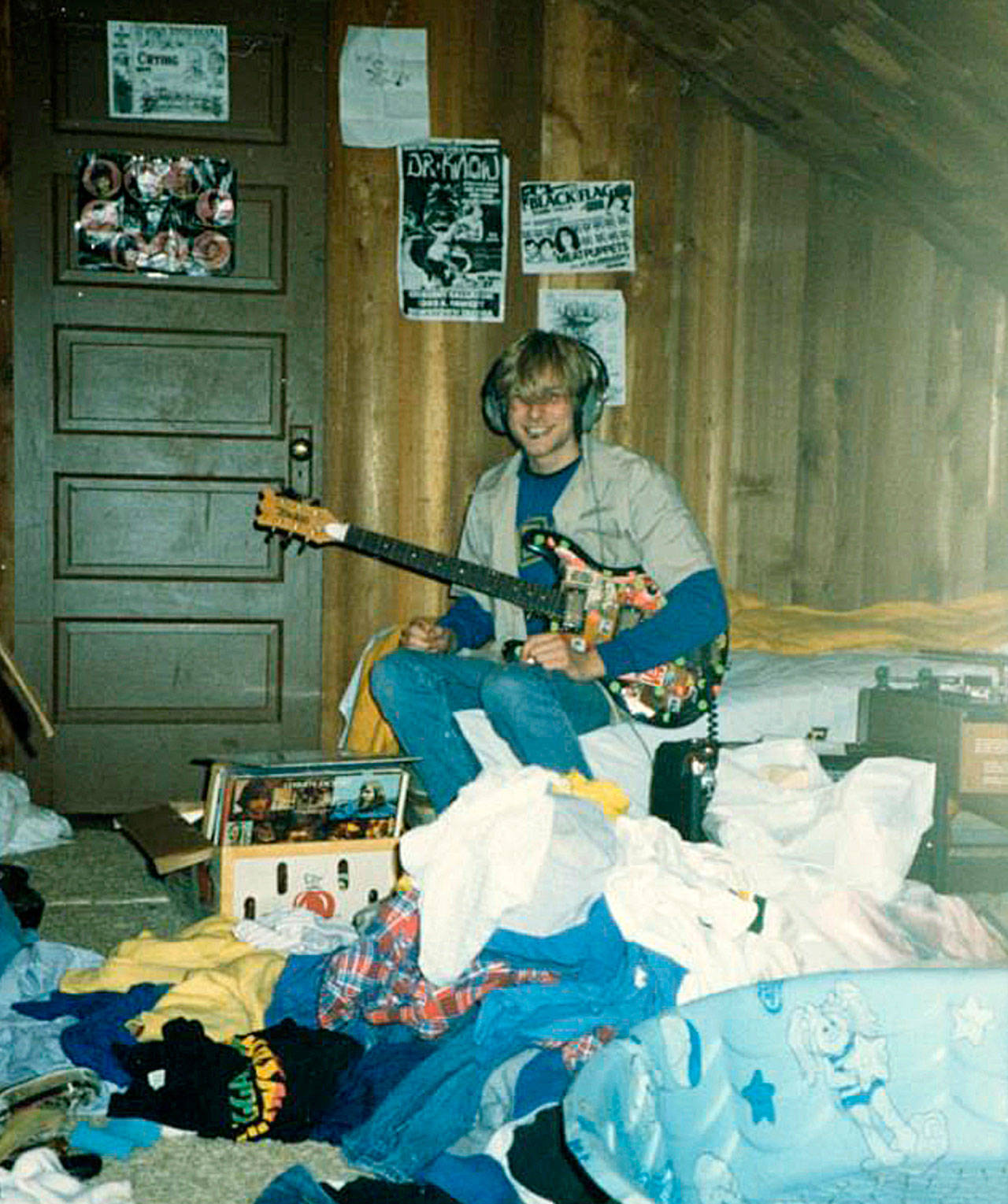 """Courtesy photo  A young Kurt Cobain and his guitar in the attic room of his childhood home on East First Street in Aberdeen, circa 1983. About eight years later, Nirvana's """"Nevermind"""" album was released."""
